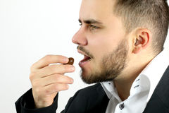 Elegant man eating chocolate. On a white background stock image