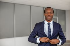 Elegant man is expressing gladness at work. Going to meeting. Waist up portrait of cheerful elegant young african businessman in formal clothes is standing in stock images