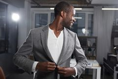 Elegant man is expressing gladness at work. Going to meeting. Waist-up of stylish cute positive young african businessman is standing in office and looking back stock photo
