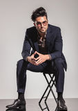 Elegant man with glasses sitting on chair stock images