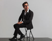Elegant man with glasses sitting and looking up Royalty Free Stock Photography