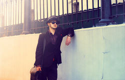 Elegant man in a hat standing near the wall Stock Photography