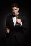 Elegant man holding a bottle and a glass of champagne. Stock Photo