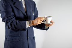 Elegant man holding a cup of coffee or tea in hands royalty free stock photos