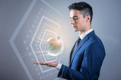 Elegant man is holding digitally generated image of globe. My location. Thoughtful young pleasant businessman is looking at 3D model of planet with geolocation stock image
