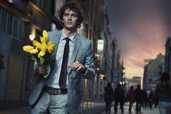 Elegant man holding flowers. And walking Stock Photos