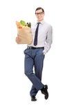 Elegant man holding a grocery bag Royalty Free Stock Photos