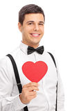 Elegant man holding a heart shaped cardboard Royalty Free Stock Photo