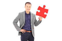 Elegant man holding a piece of puzzle Stock Images