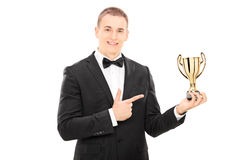 Elegant man holding a trophy Royalty Free Stock Image