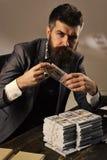 Elegant man i dräkt Man sammanträde på tabellen med högar av pengar som räknar vinst Olagligt kontant begrepp r royaltyfri foto