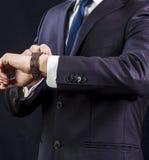 Elegant man i dräkten som ser hans klocka Arkivfoto