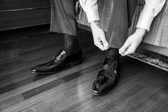 The elegant man laces shoes Royalty Free Stock Image