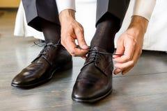 The elegant man laces shoes Stock Image