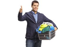 Elegant man with a laundry basket full of clothes making a thumb Stock Photography