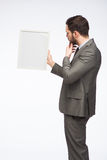 Elegant man looking at a framed board Royalty Free Stock Images