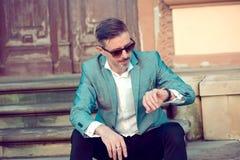 Elegant man looking at wristwatch outside Stock Image
