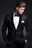 Elegant man looks to side with hands in pockets royalty free stock photo