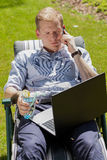 Elegant man lying on sunbed. And doing business case Stock Photo