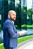 Elegant man outdoor. Handsome bearded smiling man writing notes outdoor near the office royalty free stock photos