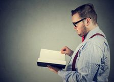 Elegant man reading a book. Side profile of a serious elegant man reading a book royalty free stock photos