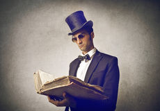 Elegant man reading. Man wearing vintage clothes and a hat reading an old book royalty free stock images
