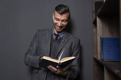 Elegant man reads book and smiles. Handsome man in suit with funny book royalty free stock photography
