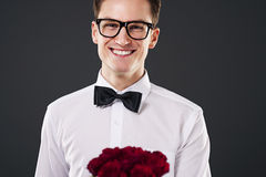 Elegant man with roses. Man wearing on glasses holding bouquet of red roses Stock Image