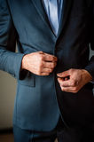 Elegant man's hands in black suit buttoning up Stock Photography