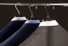 Elegant man`s suits hanging in a row Royalty Free Stock Photo