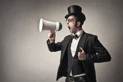 Elegant man screaming into a megaphone Royalty Free Stock Images