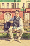 Elegant man sitting on the bench relaxing with a book Royalty Free Stock Image
