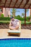 Elegant man sitting on sunbed and on the phone Stock Photography