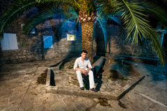Elegant man sitting under big palm on street at night Stock Images