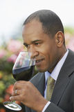 Elegant Man Smelling Red Wine. Closeup of an elegant African American man smelling red wine Stock Photos