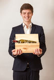 Elegant man smiling and carrying wooden box with red wine Royalty Free Stock Images