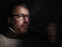Elegant man smokes a pipe. Studio shot. Royalty Free Stock Photo