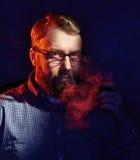 Elegant man smokes a pipe. Studio shot. Stock Image