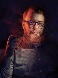 Elegant man smokes a pipe. Studio shot. Stock Photos