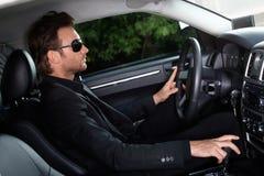 Elegant man som kör en bil Arkivfoto