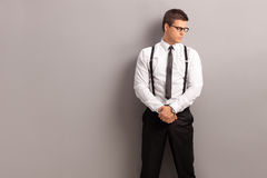 Elegant man standing against a gray wall Royalty Free Stock Image
