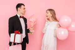 Elegant man in a suit, gives a box with a gift and a bouquet of flowers, to a beautiful woman, on a pink background. Women`s day stock photos