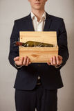 Elegant man in suit holding wooden box with wine Stock Image