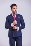 Elegant man in suit looking away while unbuttoning shirt Stock Image