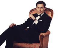 Elegant man in suit sitting on vintage armchair. Luxury. Royalty Free Stock Image