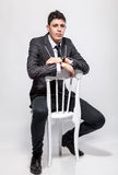 Elegant man in suit sitting on wooden chair at studio Stock Image