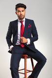 Elegant man in suit and tie sitting on a stool Royalty Free Stock Photo
