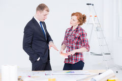 Elegant man in suit and a woman standing close to the drafting table Stock Image
