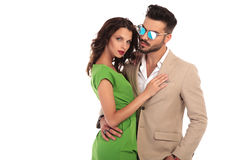Elegant man in sunglasses and suit embracing his woman. Elegant men in sunglasses and suit embracing his woman; young modern couple standing embraced on white Stock Photo