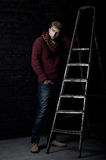 Elegant man in a sweater, jeans and a scarf Royalty Free Stock Photo